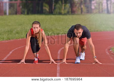 Young sport couple in starting position prepared to compete, looking ahead. Healthy fitness concept with active lifestyle.