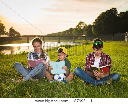Children Sitting On The Grass With Books