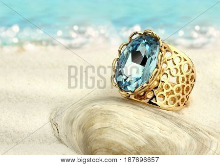 Golden ring with aquamarine on summer sand beach