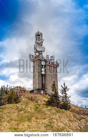 Telecommunication tower with satellite dishes and radio antennas on Postavaru peak Poiana Brasov Romania.