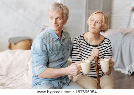 True support. Adorable nice elderly couple looking out of window while spending morning together and having some warm drinks