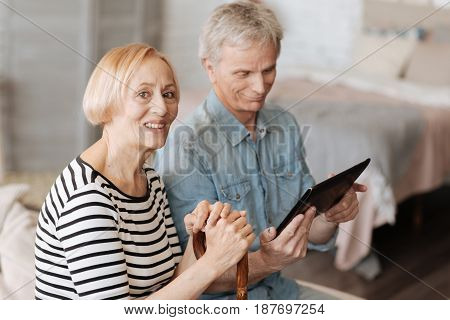 Mastering contemporary technologies. Two clever energetic elderly people enjoying their time together while watching interesting videos using the tablet