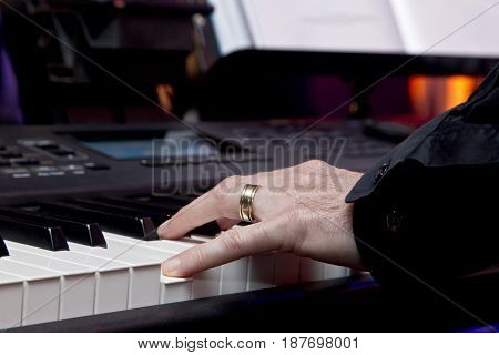 male hand playing white and black electric piano keys during a band practice