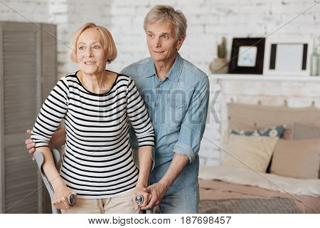 One more step. Sweet careful elderly gentleman helping his lady walking by holding her by the hands and making sure she standing firmly