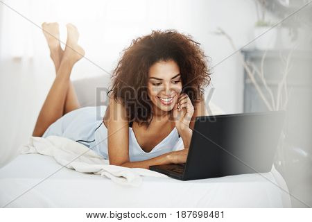 Young happy beautiful african girl in sleepwear lying on bed at home smiling looking at laptop.