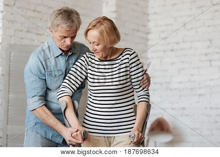 Everlasting trust. Remarkable patient strong lady recovering from an injury and using the crutches for moving while her man helping her
