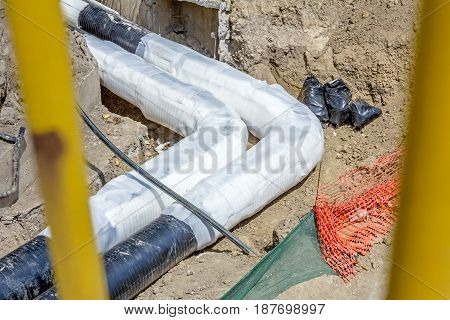 Placing set of thermal insulation on new pipeline in trench.