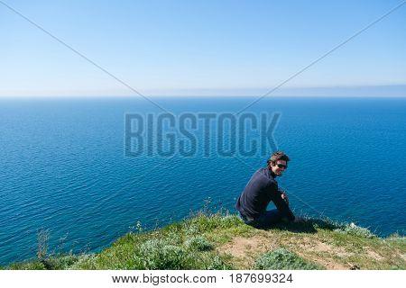 Man sitting on edge of cliff at edge.