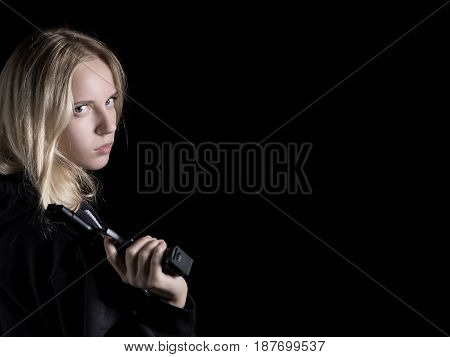 serious girl with gun on black background with copy space