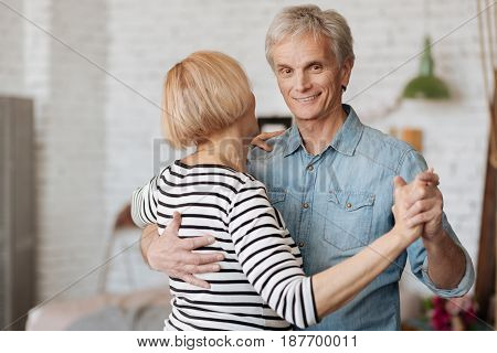 Following his lead. Tender emotional elderly gentleman feeling romantic and asking his lady for a dance while enjoying their free time together