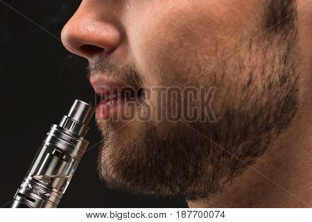 The face of vaping young man on black studio background