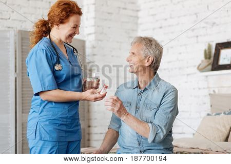 Home therapy. Neat nice prominent nurse serving her patient a glass of water and medication for recovering from disease he suffering