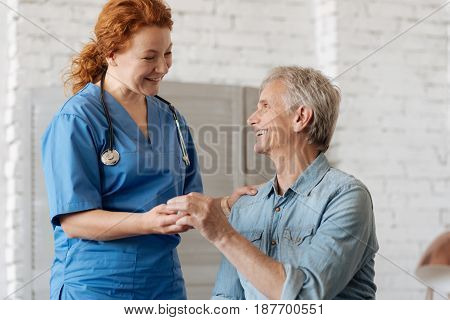 These are good for recovery. Enthusiastic energetic medical worker handing elderly man a pack of pills he needing for recovering from his illness