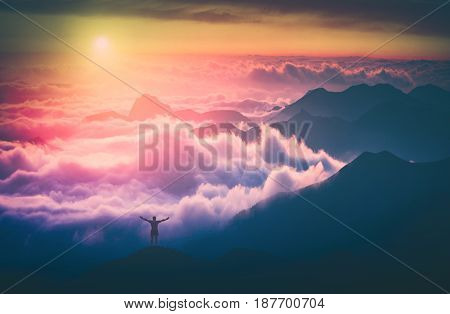 Man standing on a mountain top with rised hands and welcome sunrise in a mountains above the cloudy valley. Instagram stylisation.