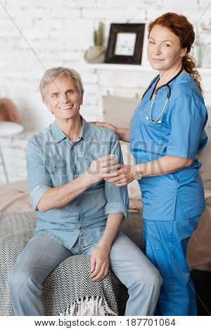 Domiciliary care. Learned competent medical worker serving her patient a glass of water for making him feel better while running a weekly consultation at home