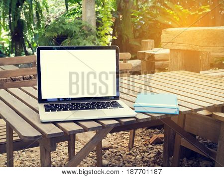 office table with blank screen on laptop and blue cover notebook paper at park.
