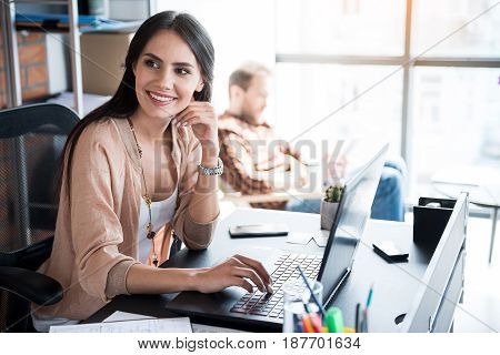 Cheerful female worker is typing on laptop and looking aside with bright smile. She sitting at table in office. Portrait