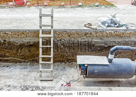 Wooden ladders are used for access into trench to welding pipeline.