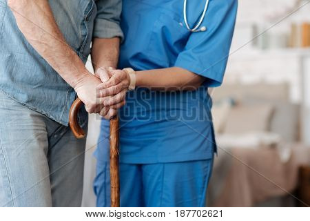 Be careful. Active productive admirable woman holding her patient by the hand making sure he standing firmly and assisting him moving around his house