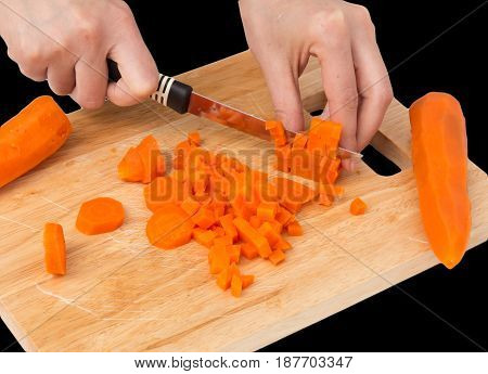 cook cuts carrots on a board on a black background .