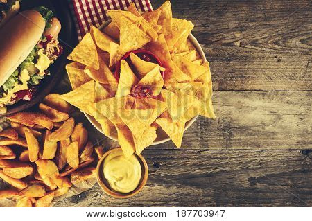 Variety of classic traditional american tasty junk unhealthy food on wooden background with copy space. Hot Dogs and Chips. Toning.
