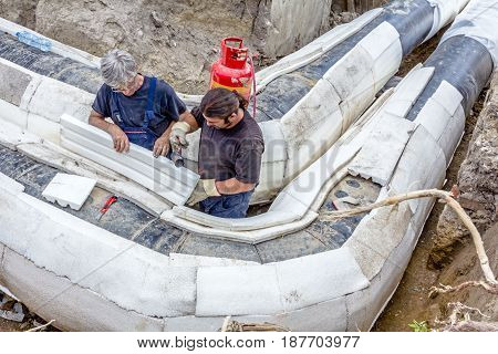 Zrenjanin Vojvodina Serbia - July 01 2015: Team of riggers is affix thermal protection on isolated pipeline gas blowpipe torch heating for melting Styrofoam.