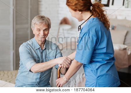 Enthusiastic vibes. Cheerful lively senior gentleman having a nurse visiting him every week for a checkup and assistance during his treatment
