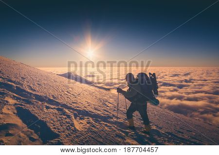 A climber with backpack climbs up a snowy slope. Sunset sky on a horison. Instagram stylisation.