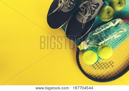 Healthy Life Sport Concept. Sneakers with Tennis Balls Towel and Bottle of Water on Bright Yellow Background. Copy Space.