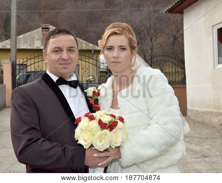 Young married couple posing for the camera outdoors