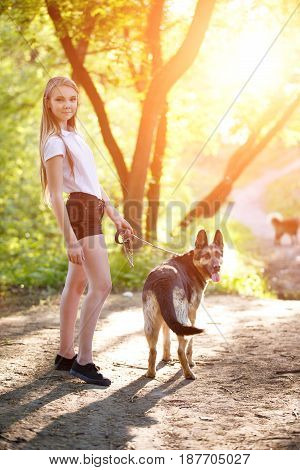 Teenage girl in white shirt with her dog sitting on pathway in the park