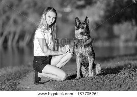 Teenage girl in white shirt with her german shepherd sitting on pathway in the park