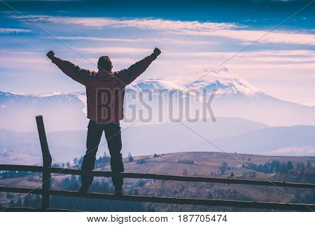 A hiker stands on a fence with raised hands in a mountain valley. Instagram stylisation.