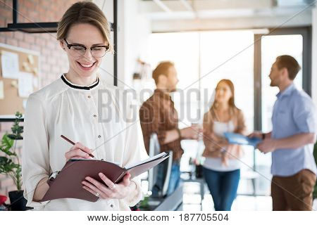 Cheerful employee is standing in office and making notes in open notebook with smile. Colleagues are having conversation