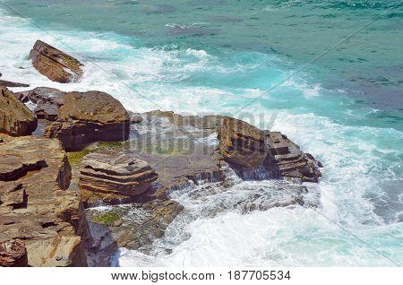 Waves crashing over sandstone rock platforms on NSW coast at Garie Beach, Royal National Park, Sydney