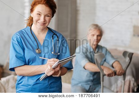 Attentive listener. Capable kind medical worker visiting her patient at home and writing down his symptoms for diagnosing him right