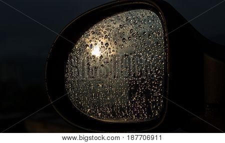 The reflection of the sun in a glass filled with drops of rain water the car's shape reflects the sun the glass a lot of water droplets