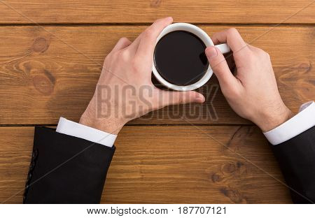 Businessman coffee break top view closeup, hands with americano cup on wood table