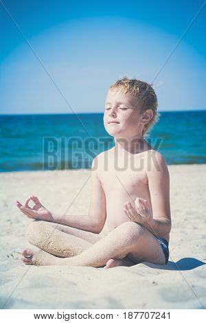 Young boy meditating on a beach near the sea in a sunlight. Instagram stylisation.