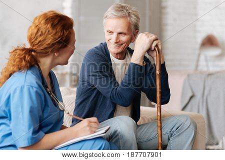 Positive consultation. Considerate neat excellent doctor asking mature gentleman about his health and noting down important fact for analyzing them and prescribing treatment