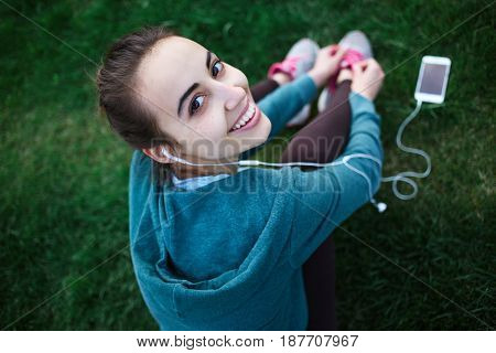 Portrait of young and sporty woman in sportswear sitting with the smartphone and headphones on the grass outside at the park on green field on cloudy day, Dnipro, Ukraine. She is sits on the green meadow between trees, Ties up shoelaces on sneakers and li