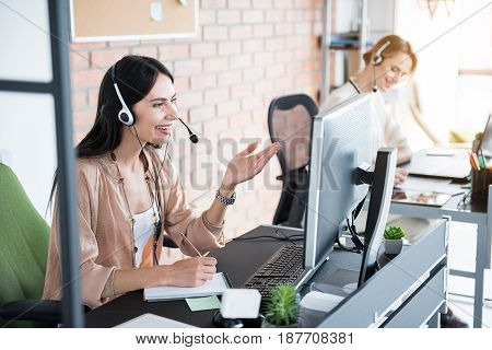 Hilarious interested female employee in headphones with microphone is looking at screen of computer. She smiling and writing on notebook. Colleague sitting near neighboring table