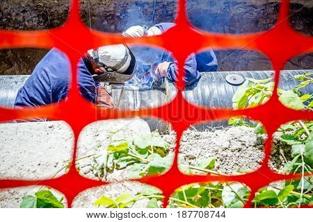 Welders are in trench they arc welding pipeline. Confined space with orange plastic safety net