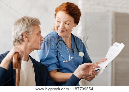 What do you mean by that. Excited graceful intelligent doctor explaining some details of the treatment procedure while conducting a consultation and helping her patient recovering