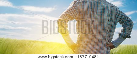 Farmer looking at the sun on the horizon over cultivated wheat crops field