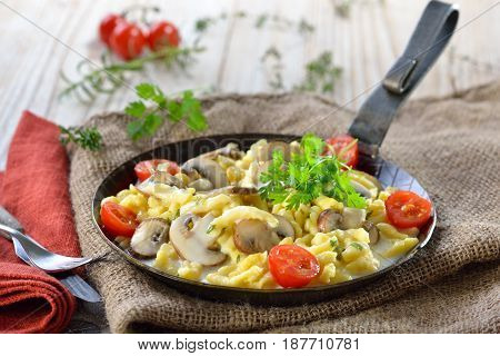 Vegetarian Swabian spaetzle with thickened cream sauce and fresh mushrooms served in an iron frying pan on a rustic table with an old jute sack