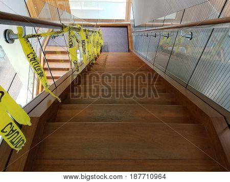 wood and glass stairs and raiil with yellow caution tape