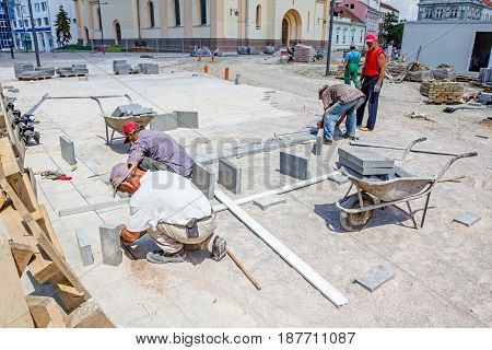 Team of masons is fitting flagstone they making footpath paving large street.