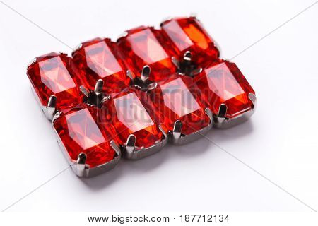 Ruby loose gemstones pattern on white background. Ornament of red mounted gems, jewelry production concept.