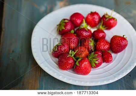 Ripe strawberries in a plate on a wooden background